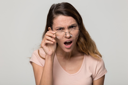 Foto de Shocked angry young woman in disbelief lowering glasses looking at camera with indignation isolated on grey blank studio background, confused girl frowning touching eyeglasses feeling flabbergasted - Imagen libre de derechos
