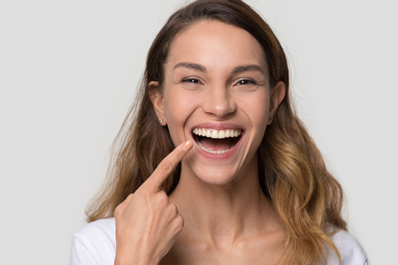 Photo pour Happy young woman with white straight teeth perfect dent orthodontic smile pointing at tooth looking at camera isolated on studio blank background, dental health stomatology service concept, portrait - image libre de droit