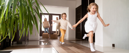 Foto de Horizontal photo happy little kids running into new home, parents with cardboard boxes on background. Loan mortgage, moving relocating concept banner for website header design with copy space for text - Imagen libre de derechos