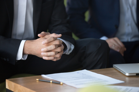 Photo for Male clasped hands clenched together, businessman at meeting negotiations or legal advice focused on listening or making decision, consulting about contract, consideration concept, close up view - Royalty Free Image