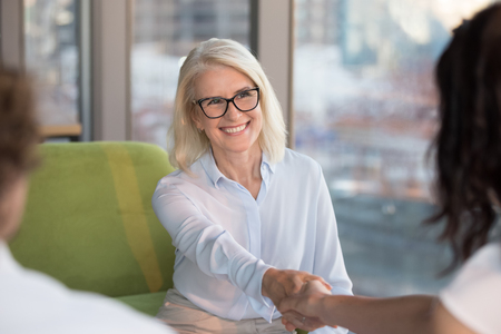 Photo for Smiling confident old mature woman job seeker applicant handshaking hr making good first impression at interview meeting, happy satisfied middle aged businesswoman shaking hand getting hired concept - Royalty Free Image