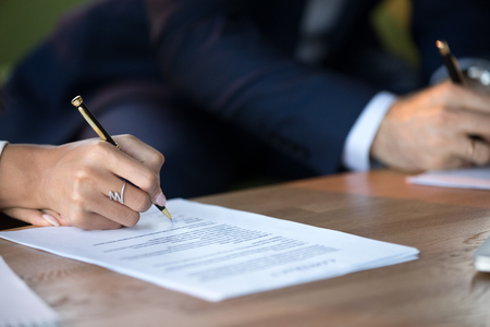 Photo pour Close up view of woman and man signing document concluding contract concept making prenuptial agreement visiting lawyer office, female and male partners or spouses writing signature on decree paper - image libre de droit