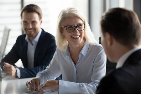 Foto de Friendly middle aged female leader laughing at group business meeting, happy old businesswoman enjoying fun conversation with partner, smiling mature business coach executive talking to colleague - Imagen libre de derechos