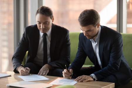Photo pour Two successful middle aged businessmen in suits signing contracts for services at meeting, satisfied male business partners put signature on legal papers making deal agreement writing on documents - image libre de droit
