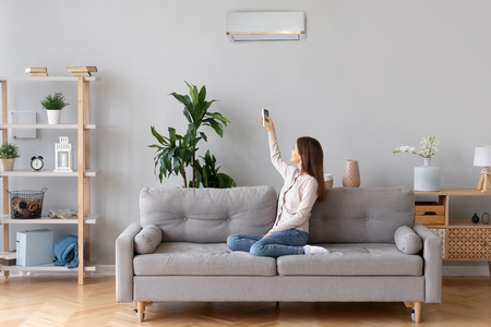 Foto de Young happy woman switching on air conditioner sitting on couch at convenient cozy home, lady relaxing on sofa in living room holding remote climate control to cooler system set comfort temperature - Imagen libre de derechos