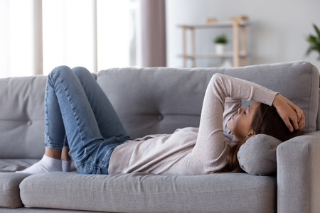 Photo for Sad depressed young woman lying on couch at home feeling headache fatigue loneliness, upset tired sick ill teen girl suffer from migraine anxiety, drowsy somnolent teenager rest on sofa after stress - Royalty Free Image