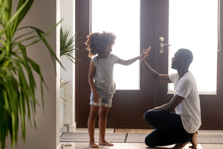 Foto de Happy black dad and little daughter giving high five in hallway at home, friendly african single father and cute kid girl clapping hands having fun deal together, daddy child friendship and trust - Imagen libre de derechos