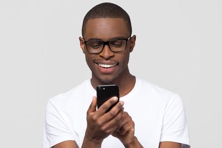 Foto de Happy young african american man in glasses using smartphone gadget social media apps, smiling black guy user holding cellphone texting sms on mobile phone isolated on white grey studio background - Imagen libre de derechos