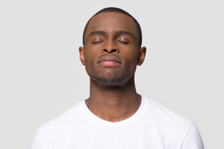 Photo for Calm mindful african american man enjoy taking deep breath of fresh air isolated on white studio background, happy black guy with serene face eyes closed meditating feeling harmony and no stress free - Royalty Free Image