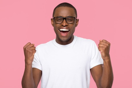 Foto de Excited overjoyed lucky black man feeling winner screaming with joy looking at camera isolated on pink studio background, african guy celebrating win triumph rejoicing victory motivated by success - Imagen libre de derechos