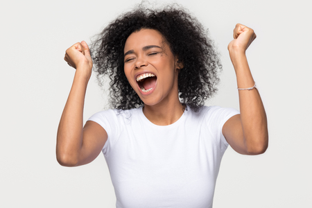 Foto de Overjoyed young african american woman screaming with joy celebrating victory win success isolated on blank grey white studio background, happy excited black girl rejoicing triumph feeling winner - Imagen libre de derechos