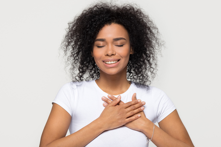 Foto de Grateful hopeful happy black woman holding hands on chest feeling pleased thankful, sincere african lady expressing heartfelt love appreciation gratitude honesty isolated on white studio background - Imagen libre de derechos