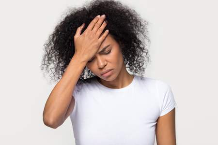 Foto de Upset young african woman touching forehead feeling headache hurt, sad ill black girl frustrated suffering from migraine fever, depressed about problem isolated on white grey studio blank background - Imagen libre de derechos