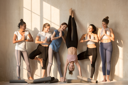 Photo pour Multiracial excited girls in sportswear stand near wall wait for yoga class having fun together, happy sportive female yogi entertain play childish practicing poses, have break in training or workout - image libre de droit