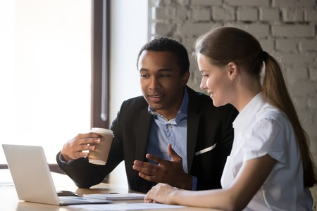 Photo for Two multiracial workers sit at office desk near laptop discussing business issues together, man and woman employee negotiate at workplace, look at computer, cooperating speak or explain ideas - Royalty Free Image