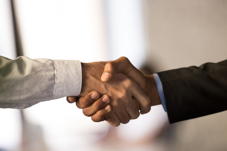 Photo for Close up of male colleagues or partners shake hands closing deal or making agreement, employees or workers handshake congratulating or greeting with success. Cooperation, partnership concept - Royalty Free Image