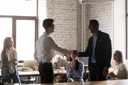 Photo for Smiling millennial businessman shake hand of male colleague congratulating with success or personal achievement, team leader handshake happy employee greeting with job promotion or employment - Royalty Free Image