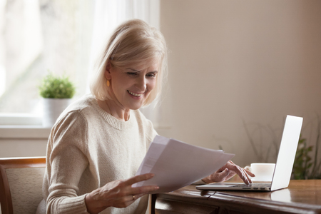Photo pour Happy blond positive aged woman sitting alone at home at desk holds received document reading good news, notification paper checking bills or bank account balance statement feeling satisfied and glad - image libre de droit
