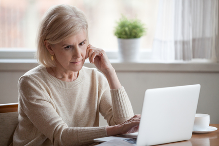 Foto de Frustrated grey hair sad middle aged woman sitting at table using computer. Distracted grandmother thinking about financial difficulties or health problems having doubts thinking feels lonely and lost - Imagen libre de derechos