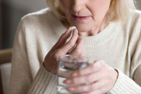 Photo pour Close up of unhealthy middle aged woman suffers from pain, holding pill and glass of still water feels ill taking medicine, cropped image. Disease prevention and treatment of old mature people concept - image libre de droit