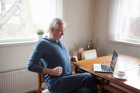 Photo pour Grey haired middle aged senior male sitting alone in the kitchen on chair stretching back after long time working on computer doing exercises for loins preventing osteoarthritis and spinal stenosis. - image libre de droit