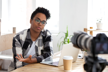 Photo for Serious african girl blogger vlogger talking to camera shooting educational video filming webinar blog, black female business coach teacher speaking recording vlog training or job interview - Royalty Free Image