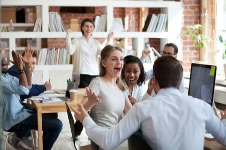 Foto de Excited diverse business team employees screaming celebrating good news business win corporate success, happy multi-ethnic colleagues workers group feeling motivated ecstatic about great achievement - Imagen libre de derechos
