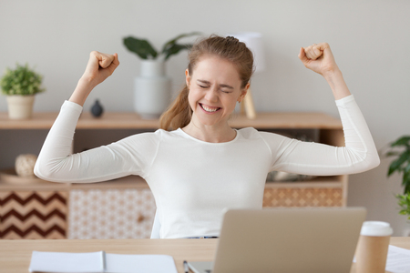 Foto de Happy young woman celebrating online win at home, excited millennial student rejoicing receiving good test exam results or college admission letter on laptop, winner satisfied with success victory - Imagen libre de derechos
