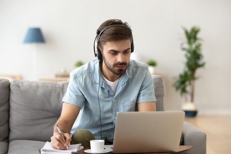 Photo pour Serious young man looking at laptop wearing headset learning foreign language, training knowledge listening webinar making notes, online study, e-coaching, distance education, e-learning concept - image libre de droit