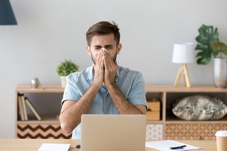 Foto de Ill at work young man got flu allergy sneezing blowing wiping running nose in tissue, allergic guy caught cold at job sitting at home office workplace having respiratory disease, sick leave concept - Imagen libre de derechos