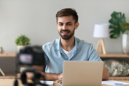 Foto de Young confident man speaker talking on digital camera recording vlog sitting at desk with laptop, male vlogger or business trainer speaking shooting blog filming reportage advertising video, coaching - Imagen libre de derechos