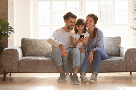 Foto de Happy family and kid daughter having fun with smartphone gadget at home, little child girl looking at phone play game using app with mom dad watching funny mobile video, making online call on couch - Imagen libre de derechos