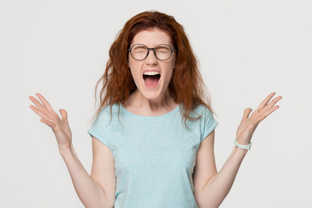 Foto de Angry mad outraged stressed young redhead hysterical girl yelling shouting loud, overjoyed excited red-haired woman with emotional face screaming with joy isolated on white grey studio background - Imagen libre de derechos
