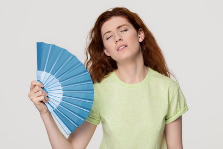 Foto de Overheated redhead woman sweating feel uncomfortable suffer from heat stroke perspiration problem, tired sweaty lady waving fan cooling in hot summer weather isolated on white grey studio background - Imagen libre de derechos