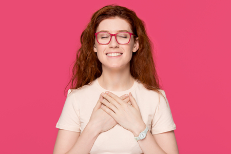 Foto de Happy grateful hopeful red-haired woman holding hand on chest close to heart feel sincere appreciation love gratitude honesty, thankful pleased touched redhead lady isolated on pink studio background - Imagen libre de derechos