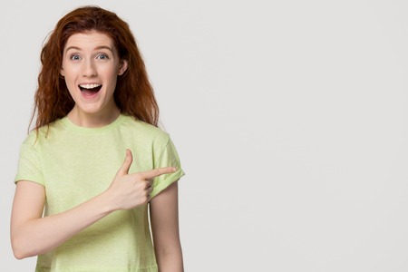 Photo for Excited thrilled redhead woman pointing finger at copy space surprised by unbelievable sale, amazed happy red-haired girl indicating advertising cheap offer isolated on white grey studio background - Royalty Free Image