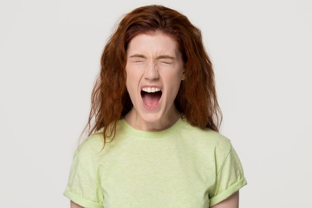 Photo pour Angry stressed hysterical redhead woman with mad emotional face screaming yelling loud with rage, crazy furious red-haired girl shouting with anger isolated on white grey blank studio background - image libre de droit