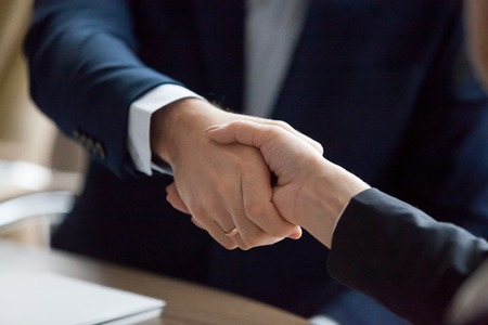 Photo pour Businessman and businesswoman in suits handshaking showing partner respect, gender equality, female male hands shake as trust loyalty collaboration concept, gratitude, good relations, close up view - image libre de droit