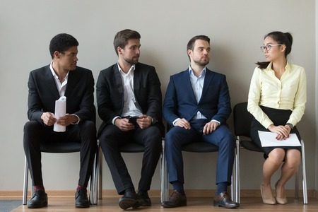 Foto de Diverse male applicants looking at female rival among men waiting for at job interview, professional career inequality, employment sexism prejudice, unfair gender discrimination at work concept - Imagen libre de derechos