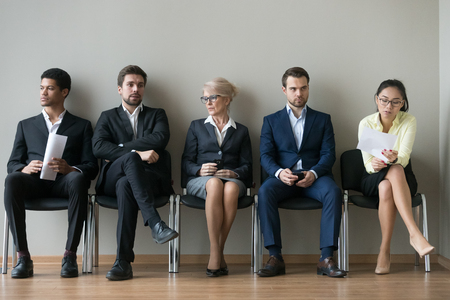 Photo for Diverse business people applicants sit in row line queue waiting for their turn, african, asian and caucasian unemployed seekers group preparing for job interview, human resources employment concept - Royalty Free Image