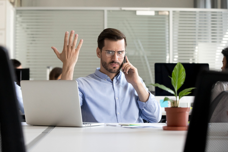 Foto de Indignant millennial employee sitting at desk in coworking space talking by mobile phone with client feels angry irritated and surprised. Office worker solves problems or business matters distantly - Imagen libre de derechos