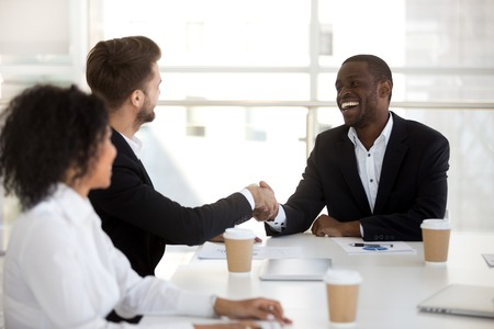 Photo for Diverse colleagues shaking hands greeting each other during briefing. Positive businessmen company owner and client handshaking expressing regard sitting together at office desk starts negotiations - Royalty Free Image