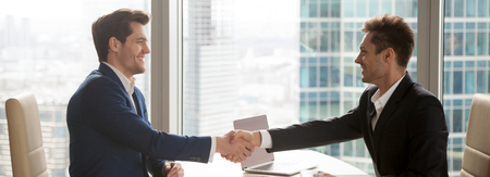 Photo for Horizontal image businessmen in formal suits handshaking meet for negotiations sitting at modern office desk, big city skyscrapers through the panoramic windows, photo banner for website header design - Royalty Free Image