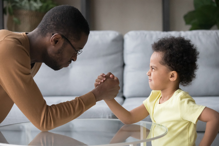 Foto de African dad and kid son with funny angry faces arm wrestling having fight showing family power, black baby sitter or father in law and stubborn child boy toddler holding hands play competing at home - Imagen libre de derechos