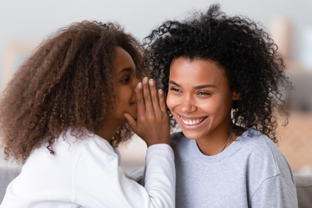 Photo pour Close up african mother best friend enjoy time gossiping with daughter, younger sister whispering secret in ear of confidant person, teenager girl chatting with nanny. Concept of trustworthy relations - image libre de droit