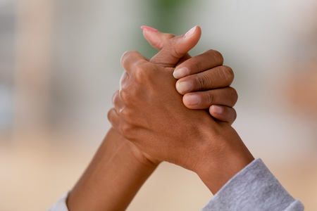 Foto de Close up african american women hold hands people having fight arm wrestling. Competition between females, daughter and mother generations confrontation, family conflicts and misunderstanding concept - Imagen libre de derechos
