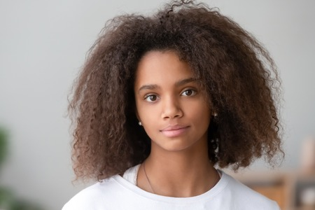Foto de Head shot portrait healthy attractive mixed race adolescent teen girl with curly ringlets hairstyle and pretty face posing indoor looking at camera. Natural beauty innocence and new generation concept - Imagen libre de derechos