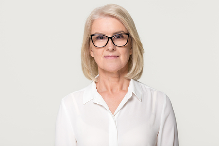 Foto de Confident older businesswoman in glasses looking at camera, middle aged senior female professional, mature lady teacher business coach head shot portrait isolated on white grey studio background - Imagen libre de derechos