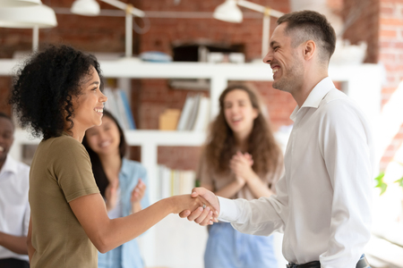 Photo for Happy african female intern worker getting hired promoted handshaking caucasian boss congratulating successful black employee by shaking clapping hand give reward bonus, gratitude recognition concept - Royalty Free Image