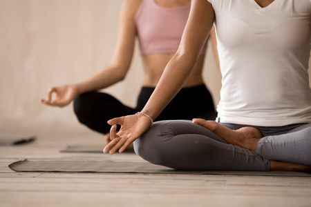 Foto de Two beautiful diverse yogi girls contemplating, doing yoga Padmasana exercise, Lotus pose, working out indoor, close up, mixed race female students training at yoga studio. Well being, wellness concept - Imagen libre de derechos